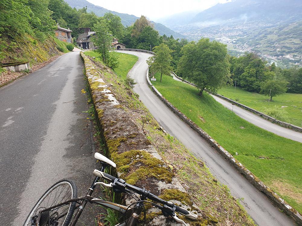 Svingete fjelleveier opp fra Valtellinadalen med en sykkel liggende over et stengjerde