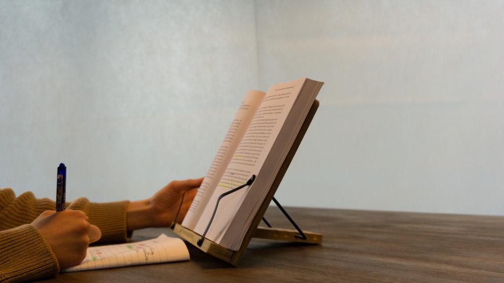 Et bokstativ som benyttes til studier, kladdebok og en pike som leser en bok som ligger på stativet