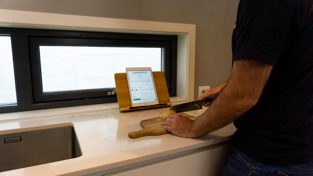 Et bokstativ som står på en kjøkkenbenk med en ipad visende oppskrift, foran ligger det en skjærefjøl med en potet på toppen som blir kuttet av en mann