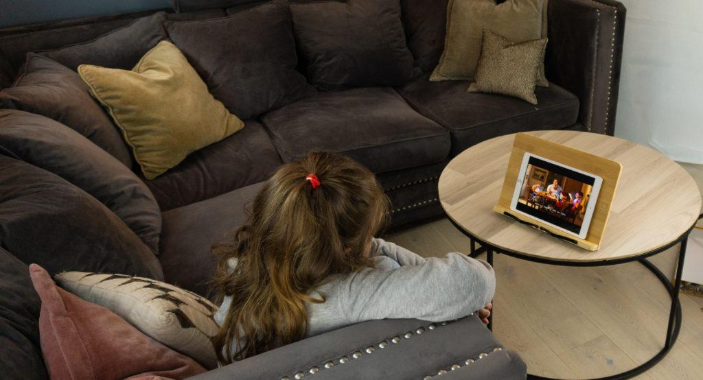 Bokstativ som er stående på et stuebord med en ipad, ung jente som sitter og ser på film på et nettbrett