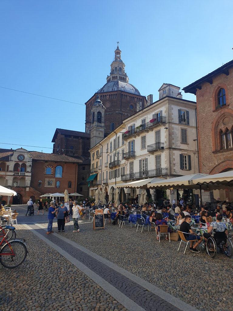 Pavia-katedralen i bakgrunnen med et hyggelig plaza med gateservering i forgrunnen