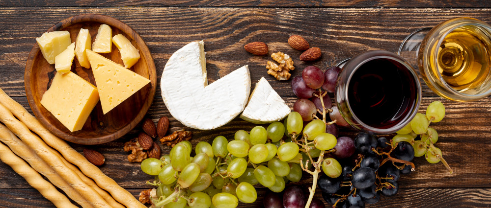 Fat med forskjellige oster druer og vin