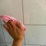 En hånd som drar en fuktet klut over en fuktet glassvegg i et dusjkabinett