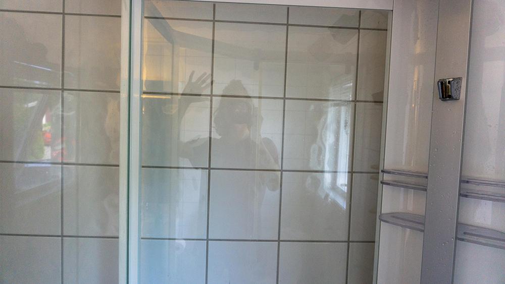Et glassvegg i et dusjkabinett som er så rent at det kan benyttes som speil, fotografen er seende i veggen vinkende til kamera
