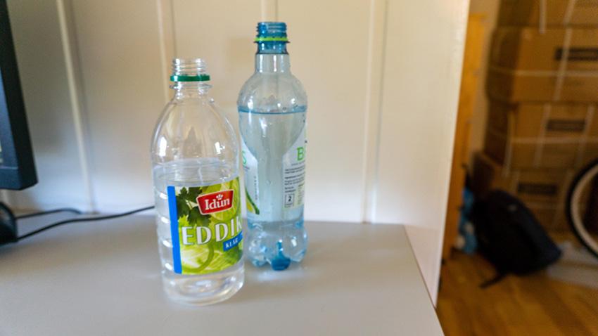 Eddik og vannflaske ved siden av hverandre, illustrerer vann og eddik som blandes 50/50 i en flaske for deretter å tilsettes litt sitronjus