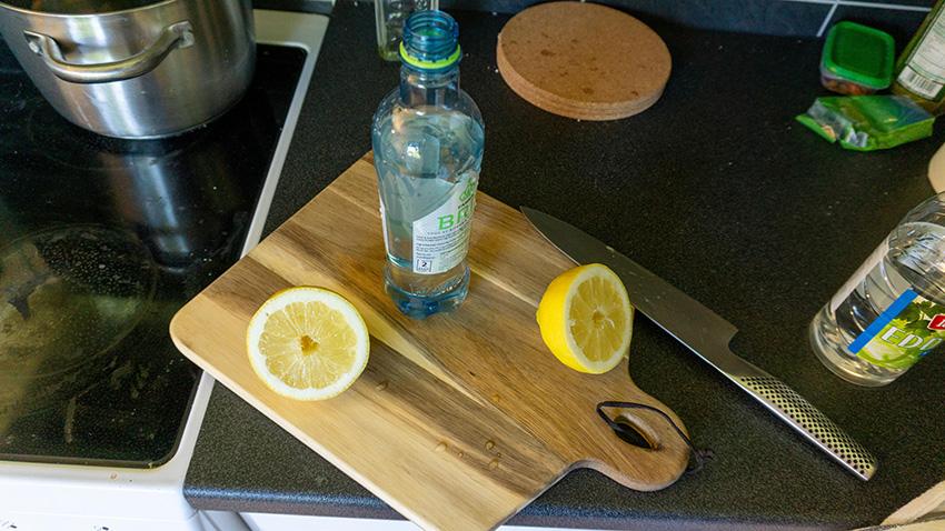 En oppskåren sitron liggende på en kjærefjøl på en kjøkkenbenk med en plastflaske ved siden der sitronjusen skal tilsettes